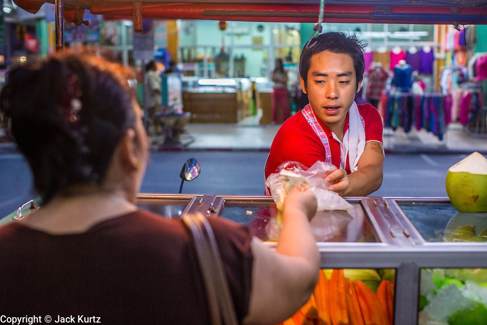 22 OCTOBER 2012 - HAT YAI, THAILAND:      A fruit vendor prepares a customer's order in the market in Hat Yai, Thailand. Hat Yai is the largest in southern Thailand. It is an important commercial center and tourist destination. It is especially popular with Malaysian, Singaporean and Chinese tourists.     PHOTO BY JACK KURTZ