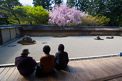 Three visitors looking at famous dry garden at Ryoanji Temple in Kyoto Japan