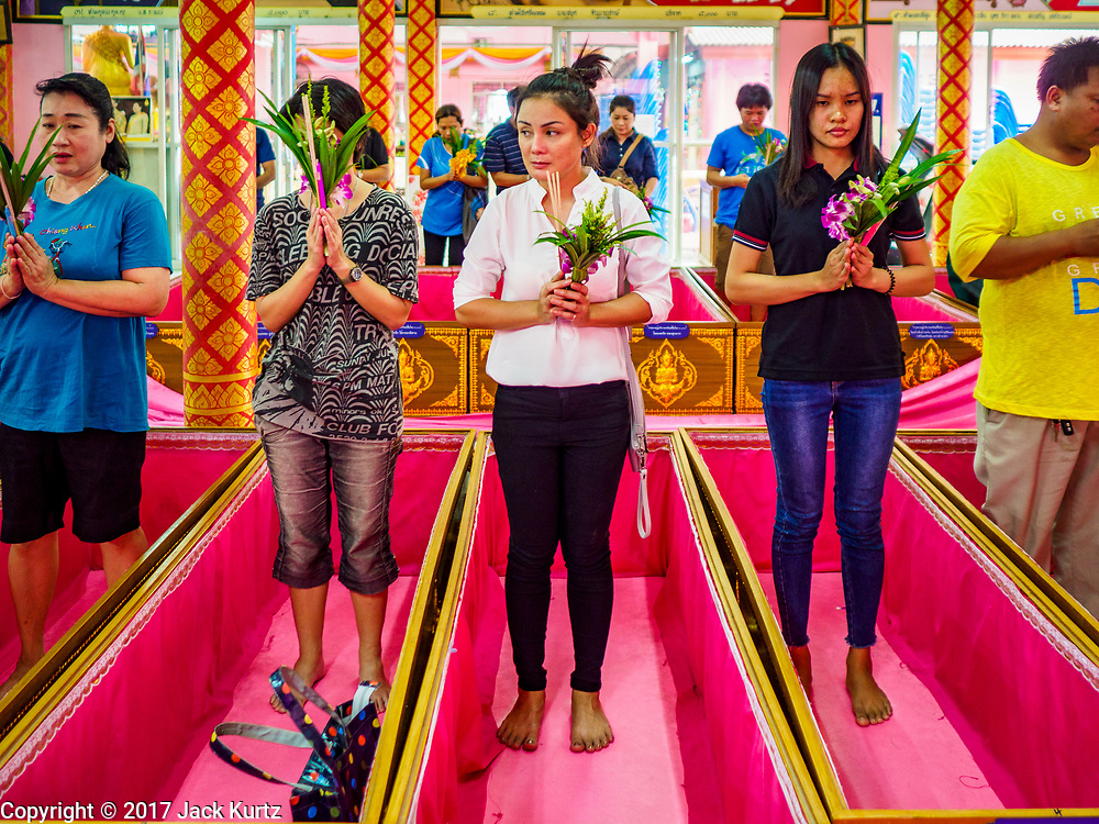 """24 JUNE 2017 - BANG KRUAI, NONTHABURI: People stand in their coffins during a """"resurrection"""" or rebirthing ceremony at Wat Ta Kien (also spelled Wat Tahkian), a Buddhist temple in the suburbs of Bangkok. People go to the temple to participate in a """"Resurrection Ceremony."""" Thai Buddhists believe that connecting people by strings around their heads, which are connected to a web of strings suspended from the ceiling, amplifies the power of the prayer. Groups of people meet and pray with the temple's Buddhist monks. Then they lie in coffins, the monks pull a pink sheet over them, symbolizing their ritualistic death. The sheet is then pulled back, and people sit up in the coffin, symbolizing their ritualist rebirth. The ceremony is supposed to expunge bad karma and bad luck from a person's life and also get people used to the idea of the inevitability of death. Most times, one person lays in one coffin, but there is family sized coffin that can accommodate up to six people. The temple has been doing the resurrection ceremonies for about nine years.     PHOTO BY JACK KURTZ"""