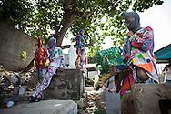 Un grupo de Diablos permanece sobre las tumbas de familiares fallecidos durante la festividad del Corpus Christi, representada en Venezuela a traves del ritual magico-religioso de los Diablos Danzantes. Los Diablos de Naiguata se identifican por pintar sus propios trajes y decorarlos con cruces, rayas y circulos, figuras que impiden que el maligno los domine. Las mascaras son en su gran mayoria animales marinos. Llevan escapularios cruzados, crucifijos y cruces de palma bendita. Naiguata, 30 Mayo 2013. (ivan gonzalez)