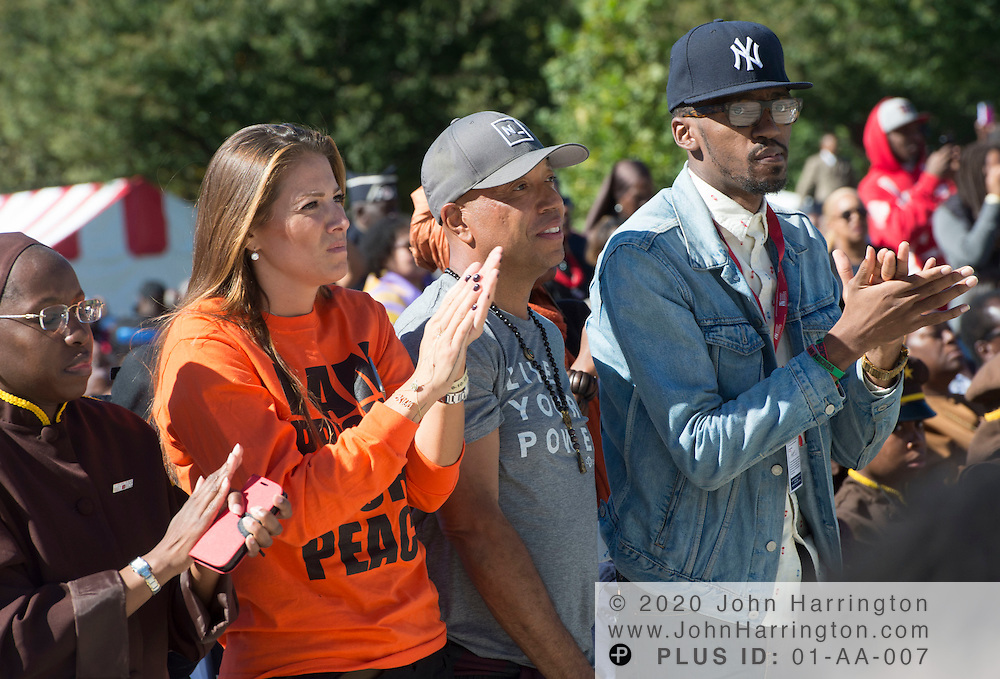 Russell Simmons (second from right) looks on as Rev. Louis Farrakhan speaks at an event marking the 20th anniversary of the Million Man March, Saturday, October 10, 2015 on the steps of the U.S. Capitol in Washington, DC.