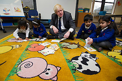© London News Pictures. 27/02/2013. London, UK.  Mayor of London BORIS JOHNSON reading books with pupils while on a visit to Reach Academy Feltham, where plans to build a new free school at a new site were announced. by Photo credit: Ben Cawthra/LNP