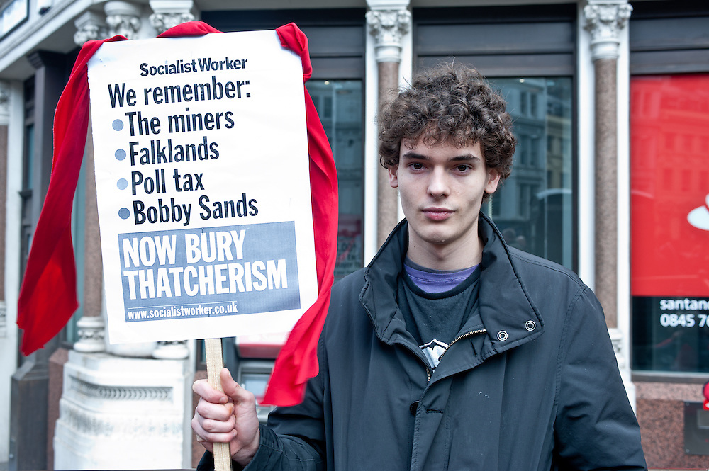 "London, UK - 17 April 2013: Luis Court, 18 from London, holds a placard reading 'We remember: the miners, Falklands, Poll Tax, Bobby Sands"" during Margaret Thatcher funeral in London"