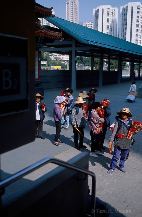 Women sell incense at the subway stop outside the Wan Tai Sin Temple in Kowloon, Hong Kong, China.