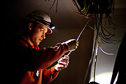 Thad Hanson, an electrician with Tradesmen Electric, routes wiring at Grant Park Village Phase II, a 167-unit apartment building under construction in Northeast Portland.