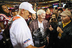 Sep 3, 2017; Landover, MD, USA; Former Virginia Tech Hokies head coach Frank Beamer presents the Black Diamond Championship trophy to Virginia Tech Hokies head coach Justin Fuente after they beat the West Virginia Mountaineers at FedEx Field. Mandatory Credit: Ben Queen-USA TODAY Sports
