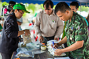 "08 JULY 2014 - WANG NAM SAP, SUPHAN BURI, THAILAND: A Thai army officers sorts sample of rice taken from a rice warehouse in Wang Nam Sap, Suphan Buri province. Representatives of the Thai ruling junta have started inspecting stocks of rice bought by the ousted civilian government following the 2012 and 2013 rice harvests. The government of ousted former Prime Minister Yingluck Shinawatra bought up thousands of tons of rice from farmers at above market prices in one of its most controversial populist policies. The alleged mismanagement of the ""rice pledging scheme,"" as it was called, was one of the factors that lead to the May 2014 coup that ousted the government. According to officials doing the inspections found rotten and weevil-infested grain, along with evidence that large stocks were replaced with old or inferior grades.     PHOTO BY JACK KURTZ"