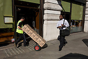 An educated businessman walks past a manlual labour delivery man tilting boxes of Coca-Cola on a trolley in London street.
