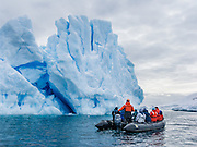 People in a Zodiac boat cruise by a blue iceberg rising in the Southern Ocean offshore from Graham Land, the north part of the Antarctic Peninsula, Antarctica.