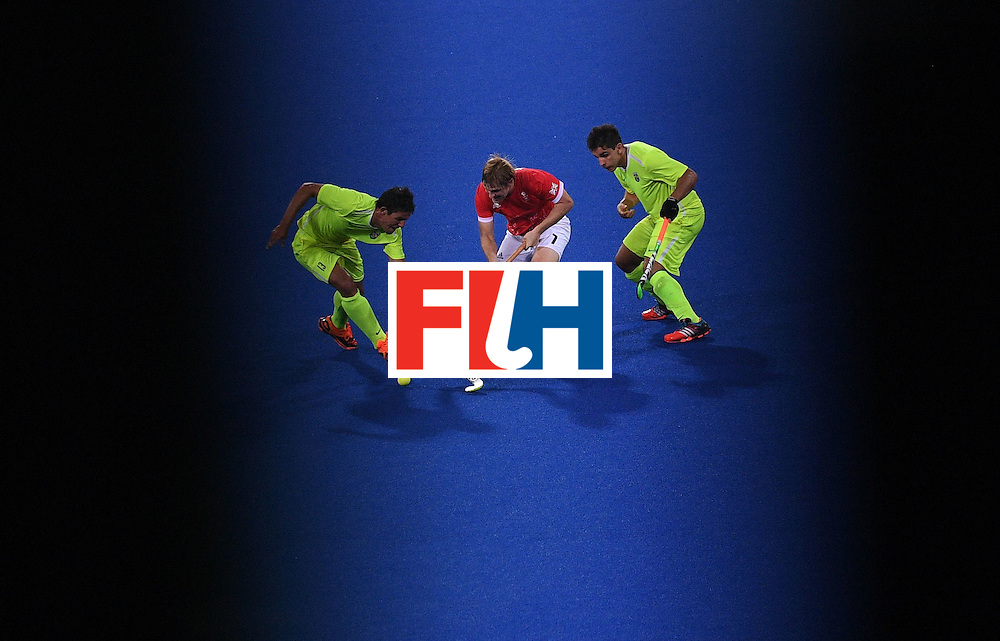 Brazil's Bruno Bitencourt (L) and Joaquin Lopez vie for the ball with Britain's Ashley Jackson (C) during the men's field hockey Brazil vs Britain match of the Rio 2016 Olympics Games at the Olympic Hockey Centre in Rio de Janeiro on August, 9 2016. / AFP / MANAN VATSYAYANA        (Photo credit should read MANAN VATSYAYANA/AFP/Getty Images)