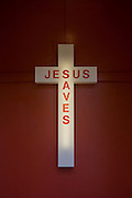 A Jesus Saves neon sign in the entrance of an evangelical church in Peckham, south London. Nearby are the voices and cries of the faithful, gathered on Easter Sunday, an important date in the Christian calendar. The cross is mounted on the inside wall, illuminated by its neon tube inside the plastic outer casing.