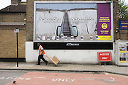 Delivery workman an the anti-EU 'UK Independence Party's (UKIP) political billboard shows an escalator leading up the white cliffs of Dover (a metaphor for unrestricted immigration access to Britain) in East Dulwich - a relatively affluent district of south London. The ad is displayed before European elections on 22nd May and UKIP's controversial right-wing policy of no foreigners into the UK to take British jobs, is promising to do well in the forthcoming election.