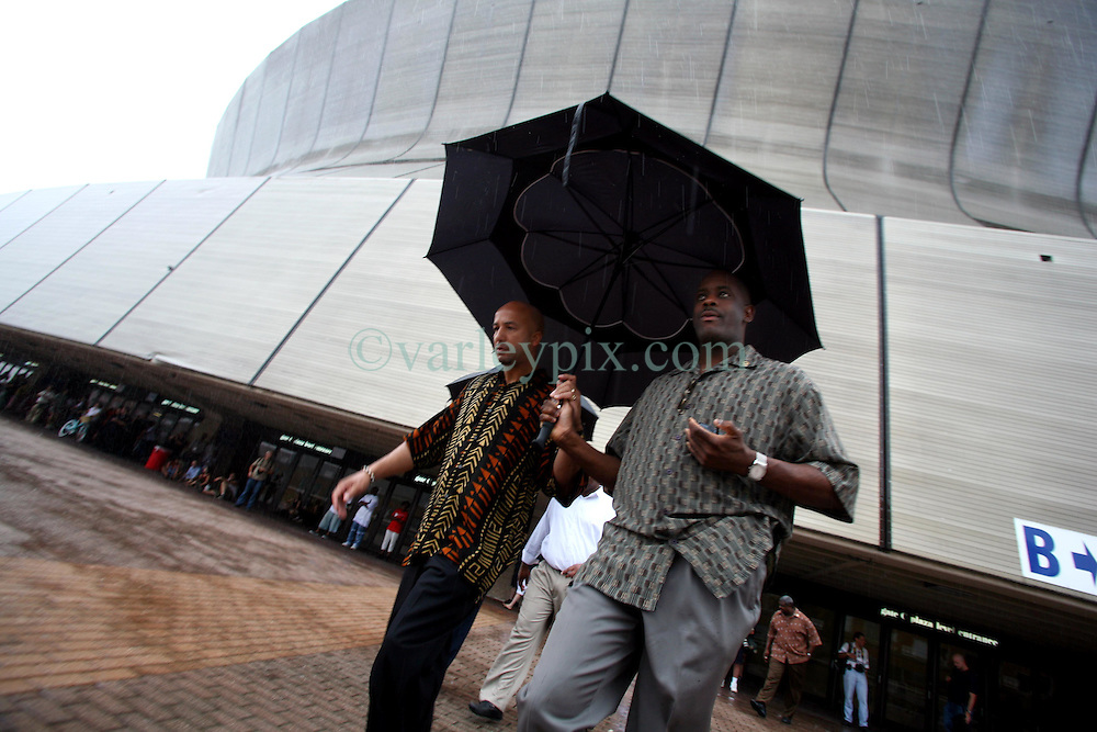 26 August  2006 - New Orleans - Louisiana. Superdome. <br /> Mayor Ray Nagin (l) arrives to give his speech in the pouring rain at the 'Hands around the dome' memorial to the victims of hurricane Katrina and to pay homage to all those who suffered so greatly inside the Superdome in the desperate days after the storm smashed the city.<br /> Photo; Charlie Varley/varleypix.com