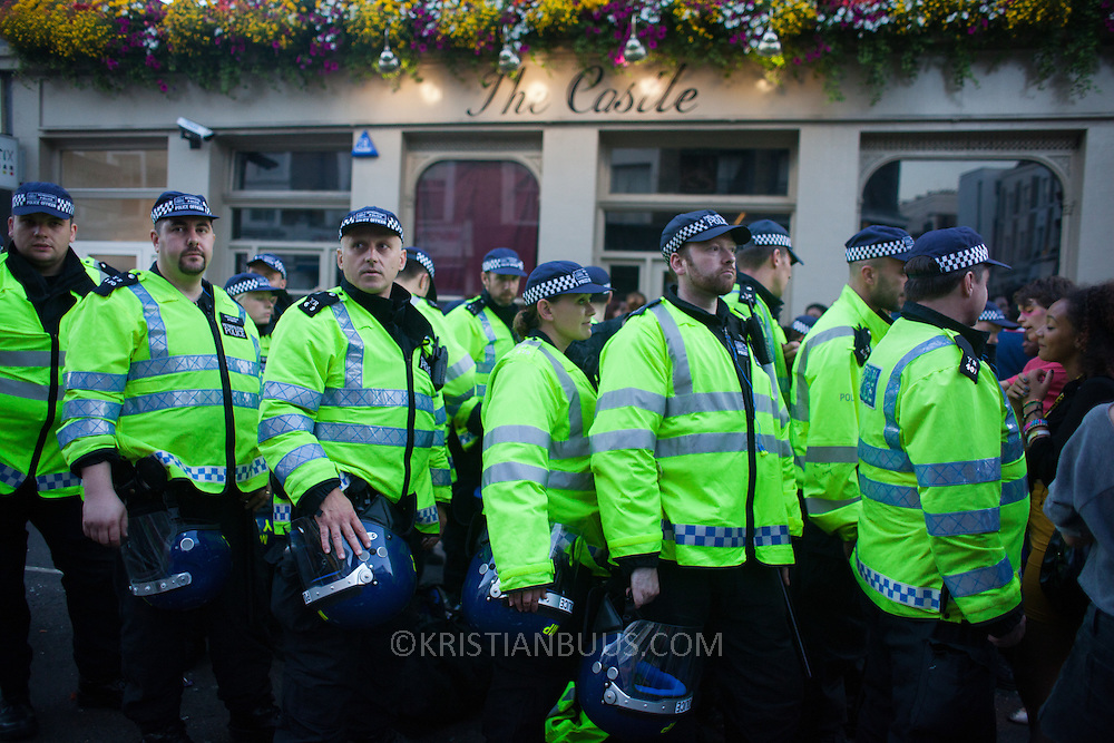 Police officers in riot gear line up outside the Castle in Portobello Road. The Notting Hill Carnival has been running since 1966 and is every year attended by up to a million people. The carnival is a mix of amazing dance parades and street parties with a distinct Caribbean feel.