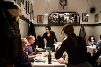 ROME, ITALY - 6 January 2014: Waitresses serve main courses to customers having dinner at Primo al Pigneto restaurant, opened by Chef Marco Gallotta in 2006 in the Pigneto neighborhood of Rome, Italy, on February 6th 2014.