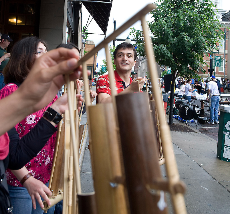 Sinan Kordon, of Turkey, plays a Angklung with some friends.  Angklung is  a musical instrument originating from Indonesia and was being offered to fair patrons during the International Street Fair Saturday.
