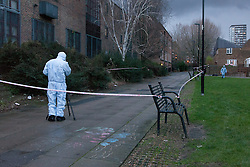 © Licensed to London News Pictures. 30/12/2012. London, UK. A member of the Metropolitan Police forensic team photographs the crime scene of a stabbing in Wapping Woods, East London where a woman was attacked on 29 December 2012. This is the second stabbing in Wapping Woods this month. Photo credit : Vickie Flores/LNP