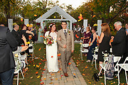 A bohemian bride and groom walking down the aisle on their wedding day as guests throw Fall leaves over their heads -- The ceremony took place at Dibbles Inn in Vernon , NY