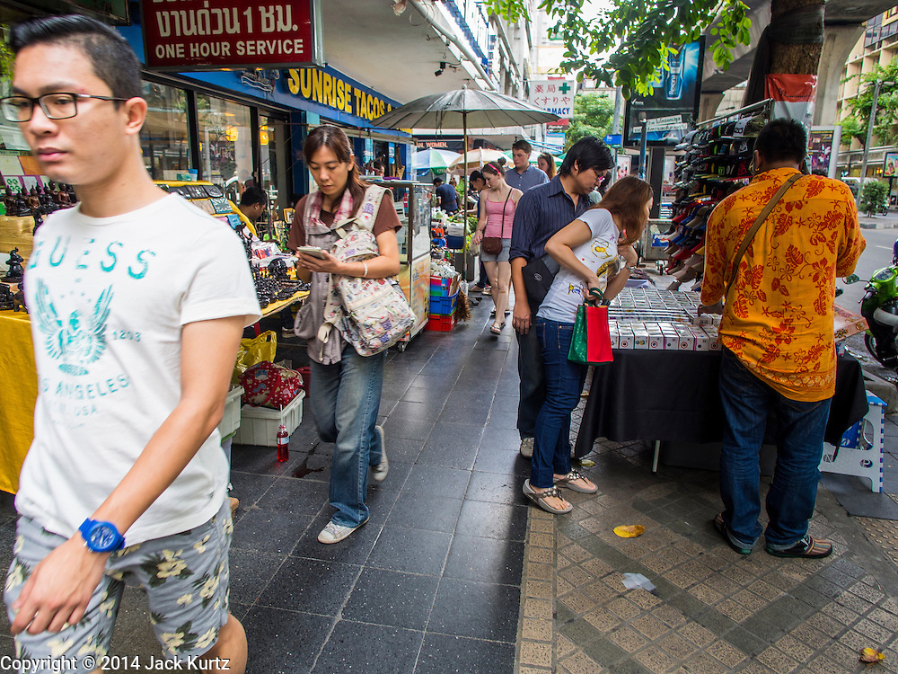 22 AUGUST 2014 - BANGKOK, THAILAND:      People walk among curio and souvenir  vendors on the sidewalks along Silom Road in Bangkok's Central Business District. The Thai military junta, formally called the National Council for Peace and Order (NCPO), has ordered street vendors off of the sidewalks in an effort to bring order to Bangkok's chaotic sidewalks. Vendors have complained that the new regulations are hurting them economically but largely complied with the military orders.      PHOTO BY JACK KURTZ