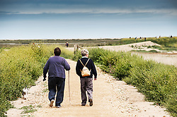 Friends walking along a track at Blakeney. Norfolk
