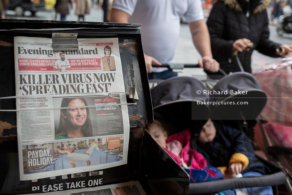 Two children are pushed in their child buggies past London Evening Standard newspapers with a headline about the latest on the rapid spread of the Chinese-source killer Coronavirus on their front pages, at Victoria station, on 30th January 2020, in London, England.
