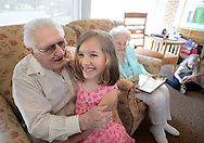 From left, Harvey Kratz, 97 shares a laugh with his granddaughter Lily Rich, 5 as his wife Mae Kratz, 96, looks on in the background  as another granddaughter, Whitney Mann sits on the floor Sunday April 17, 2016 in Hatfield, Pennsylvania. They celebrate their 80th wedding anniversary on Monday April 18th, 2016. The couple has 3 children, 9 grandchildren, 16 great grandchildren and 6 great great grandchildren. (Photo by William Thomas Cain)