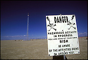 Amateur rocket launch warning sign. Launch of a rocket during the annual Black Rock X amateur rocketry event in the Black Rock desert, Nevada, USA. This huge flat expanse of land is a popular launch site for large and powerful amateur rockets as it is far from civilization and has little natural animal or plant life.