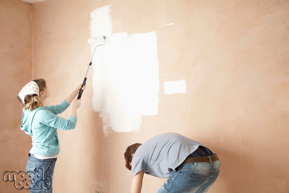 Couple using paint rollers on interior room