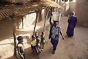 Because the household's second wife, Fatoumata Toure, is still nursing her newest baby, Pama Kondo, the household's first wife, carries all the water from the village well for the family's use. This morning, the water has an immediate use: bathing the children in her family courtyard. In the village of Kouakourou, Mali, on the banks of the Niger River. Published in Material World, page 19.