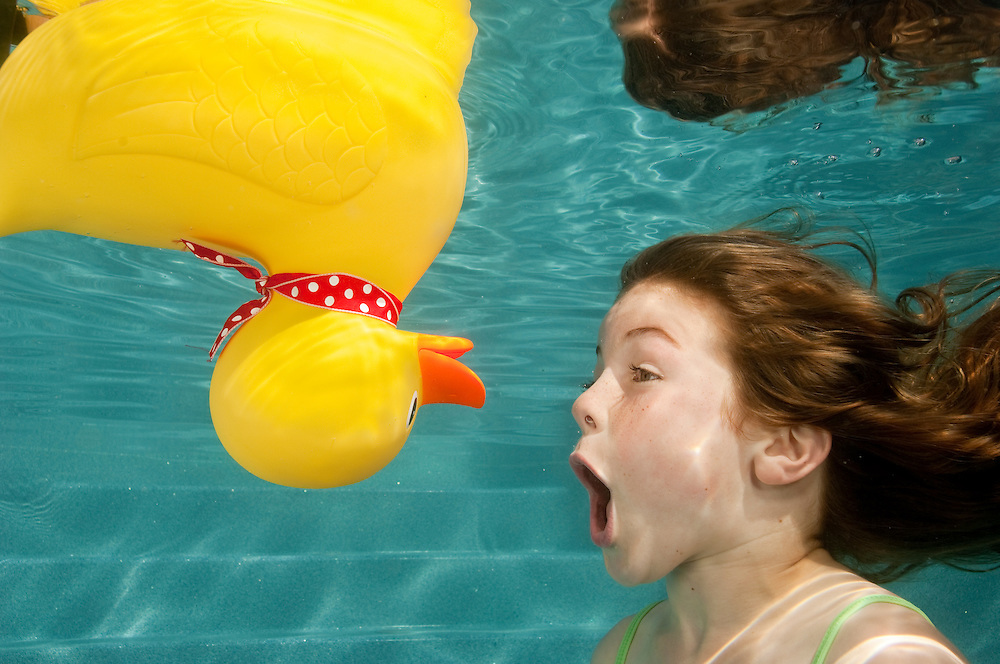 litle girl playing underwater with large yello rubber duck