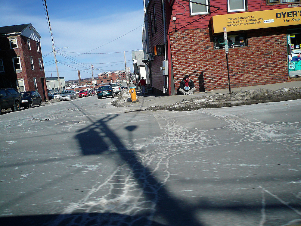 Man sitting on sidewald, maybe homeless, with shadow from window of car.