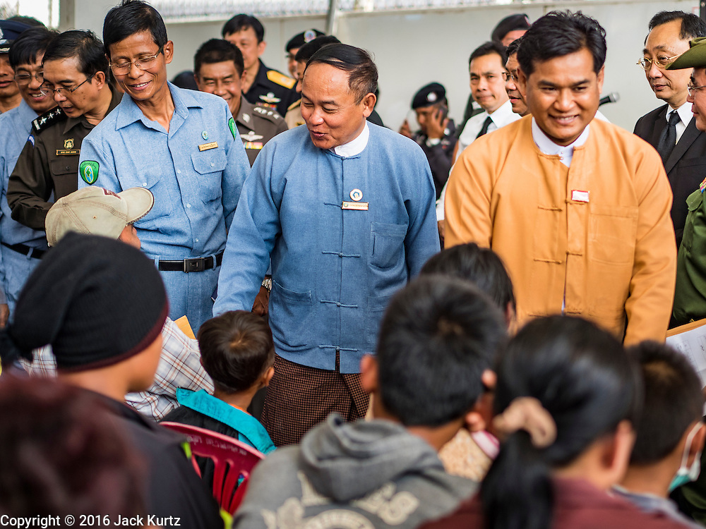26 OCTOBER 2016 - MAE SOT, TAK, THAILAND: Government officials from Myanmar greet Burmese refugees being repatriated to Myanmar from the Nupo Temporary Shelter refugee camp in Thailand. Sixtyfive Burmese refugees living in the Nupo Temporary Shelter refugee camp in Tak Province of Thailand were voluntarily repatriated to Myanmar. About 11,000 people live in the camp. The repatriation was the first large scale repatriation of Myanmar refugees living in Thailand. Government officials on both sides of the Thai / Myanmar border said the repatriation was made possible by recent democratic reforms in Myanmar. There are approximately 150,000 Burmese refugees living in camps along the Thai / Myanmar border. The Thai government has expressed interest several times in the last two years in starting the process of repatriating the refugees.      PHOTO BY JACK KURTZ