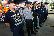 "26 SEPTEMBER 2014 - PATTAYA, CHONBURI, THAILAND: STEVE MANDALA, a volunteer with the Foreign Tourist Police Assistants (FTPA) falls into formation with other Tourist Police officers at the start of their shift on Walking Street in Pataya. Pataya, a beach resort about two hours from Bangkok, has wrestled with a reputation of having a high crime rate and being a haven for sex tourism. After the coup in May, the military government cracked down on other Thai beach resorts, notably Phuket and Hua Hin, putting military officers in charge of law enforcement and cleaning up unlicensed businesses that encroached on beaches. Pattaya city officials have launched their own crackdown and clean up in order to prevent a military crackdown. City officials have vowed to remake Pattaya as a ""family friendly"" destination. City police and tourist police now patrol ""Walking Street,"" Pattaya's notorious red light district, and officials are cracking down on unlicensed businesses on the beach.     PHOTO BY JACK KURTZ"