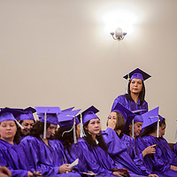 Guadalupe Lozano stands up to look around the hall as she and her fellow graduates take their seats for the New Life Learning Center graduation ceremony Friday at Lighthouse Church in Gallup.