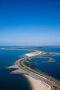 Nederland, Zeeland, Brouwershaven, 12-06-2009; de Brouwersdam, onderdeel van de Deltawerken (1971), tussen Goeree en Schouwen (aan de horizon, provincie Zeeland), links het Grevelingenmeer en in het midden Middelplaat met recreatiecentrum en vakantiepark Port Zelande. .Na het afsluiten van de zeearm Grevelingen zijn gaandeweg ernstige milieuproblemen in het nieuwe zoetwater ontstaan. De reeds in 1978 extra gebouwde doorlaatsluis, de Brouwerssluis (bij de uitstulping), heeft onvoldoende verlichting gebracht, er zijn nu plannen om een opening in de dam te maken om zo het getij deels terug te laten keren. The Brouwersdam, connection between the provinces Zeeland and Zuid-Holland is causing environmental problems, because the salt water cannot enter any longer. An opening in the dam is considered..Swart collectie, luchtfoto (toeslag); Swart Collection, aerial photo (additional fee required).foto Siebe Swart / photo Siebe Swart