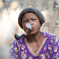 A tribal woman smoking her tobacco in a pipe at the Saturday market in Banderban, a major town in the Chittagong Hill Tracts, Bangladesh