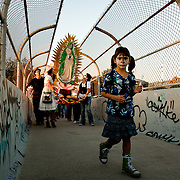 Participants of a procession cross streets on a pedestrian overpass at the Self Help Graphics Dia de los Muertos event, held on November 11, 2009, in East Los Angeles, California. Photo by Jen Klewitz