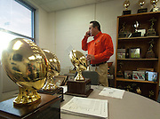 Surrounded by his teams' trophies, Aledo head football coach and athletic director, Tim Buchanan, talks on the phone with a college coach while faxing national letters of intent to the various colleges Aledo High School's 10 athletes will be attending on Wednesday February 1, 2012 morning from his office at Aledo High School, in Aledo, Texas. ..Special Contributor/Robert W. Hart