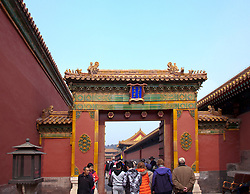 People passing through the Gate of Flourishing Blessings (architectural detail), Forbidden City, Beijing, China.  Built from 1406 to 1420 and containing more than 8,000 structures, the Forbidden City served as the residence and seat of government for the monarchs of both the Ming and Qing dynasties until 1911. Finally opened to visitors in 1925 as a public museum, it became a UNESCO World Heritage Site in 1987.