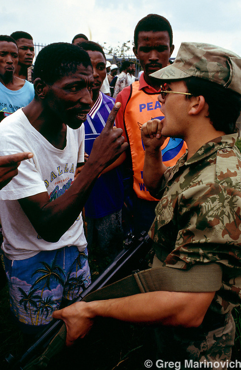 Bekkersdal Township, South Africa, Feb 1994: Residents confront a riot policeman as they patrol during three way clashes between security forces, ANC members and  AZAPO supporters in the far West Rand township of Bekkerdal, South Africa.