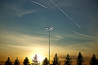 Jets leave contrails in the sky as they the sun sets behind a stand of trees at the Coeur d'Alene High School football field Wednesday, Nov. 9, 2011.