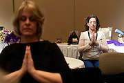 Debbie Almstel (right) and Rose Anna Kolar (left) participate in a group yoga session during the Women in Philanthropy conference on Thursday, March 14th in Baker Ballroom. Photo by: Ross Brinkerhoff.