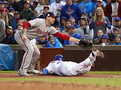 October 11, 2017 - Chicago, IL, USA - The Chicago Cubs' Willson Contreras slides safely under Washington Nationals first baseman Ryan Zimmerman with a single in the fourth  inning of Game 4 of the National League Division Series at Wrigley Field in Chicago on Wednesday, Oct. 11, 2017. (Credit Image: © Nuccio Dinuzzo/TNS via ZUMA Wire)