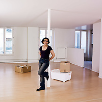 woman alone smiling inside an empty loft appartement
