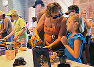 Joyce McDonnell (from left), of Atkins, looks at a clay vase with her granddaughter, Samantha Beatty, 7, of Ankeny, part of The Empty Bowls project during the 20th Annual Marion Arts Festival at City Square Park in Marion on Saturday, May 19, 2012. The Empty Bowls project features ceramic items made by Linn County students in grades K-12. The proceeds from the project will help support the Churches of Marion Food Pantry, the Linn Community Food Bank, and Mission of Hope. (Stephen Mally/Freelance)