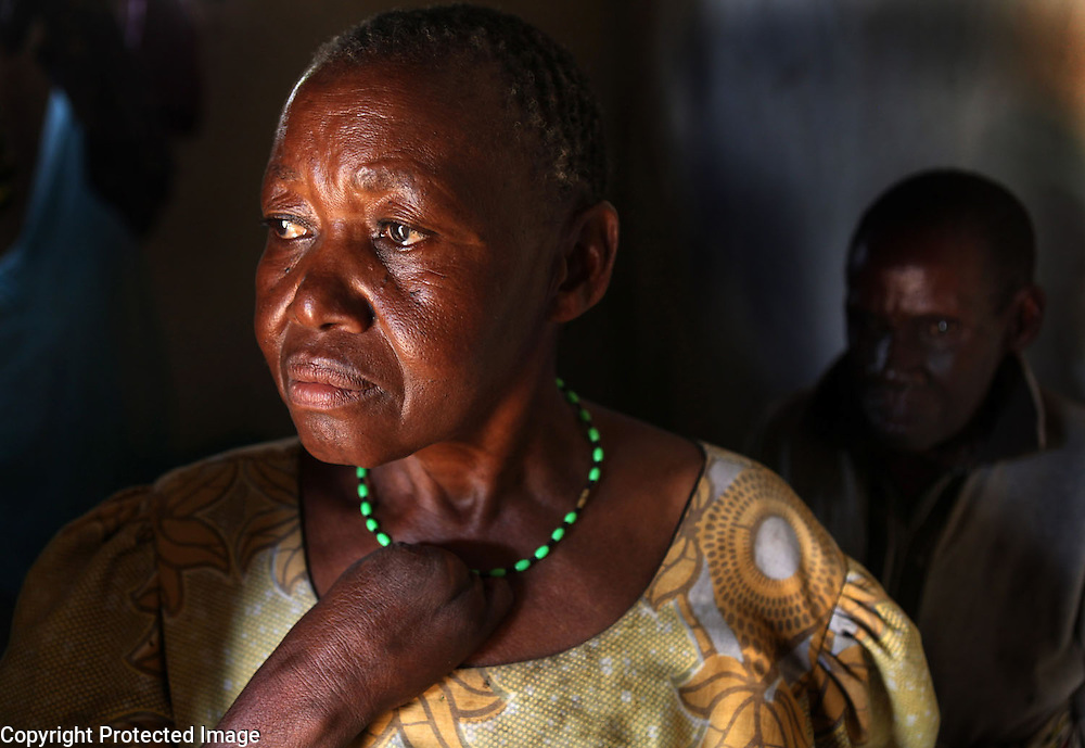 Sayi Mwandu, 56, who had part of her hand cut off by fellow villagers, stands in the doorway of her room in Kolandoto, a protective institution in Shinyanga, Tanzania. Mwandu was accused of being a witch after her eyes turned red from over-exposure to smoke from cooking fires. Mwandu is not alone in her victimization. Older women in many parts of the world, including Tanzania, are still persecuted and accused of witchcraft.  Many are killed.  Often, the accusations are an attempt to oust the woman from property the accusers hope to gain access to. Behind Mwandu is her roommate.