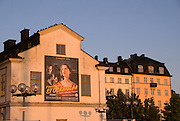 The sunrise of late summer casts a glow on the buildings in the Slussen area of Stockholm, Sweden. A large poster advertising an exhibition at Stockholms Satdsmuseum (City Museum) blends into its environent.