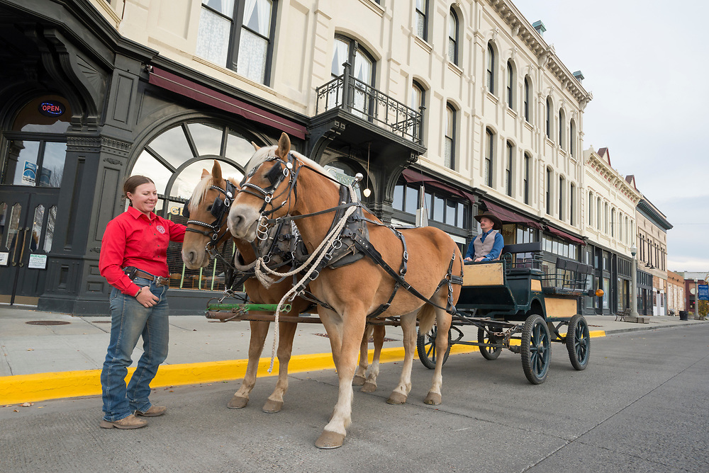 Couple with horse drawn buggy in front of the historic Geiser Grand Hotel in downtown Baker City, Oregon.