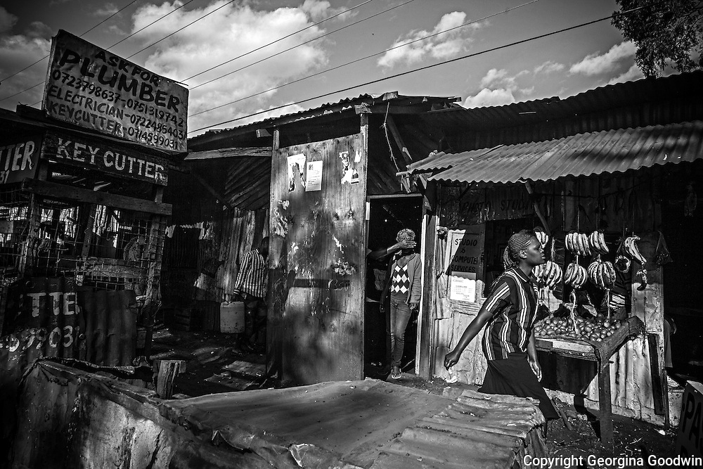 View on Mugumoini's main road Kitengela Street of the front street entrance to the 24-hour licensed bar &quot;Mark 1&quot; off Mugumoini's main road Kitengela Street on a normal day. Standing in the doorway is Winnie, 24, a prostitute who was raped one night on her way back from a pub just outside the Mugumoini Village area. <br />