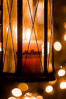 An old fashioned lantern and bright lights create a symbolic Christmas season type image.
